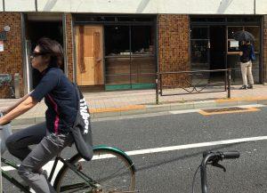湯立て坂を下って千川通りにぶつかる手前。自転車が走り、店内をのぞくひとも。