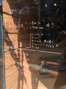 透明なガラスに白い手書き文字でメニューや営業時間が書かれています。
