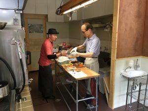 厨房で働く植村さんと帽子をかぶったパティシエ